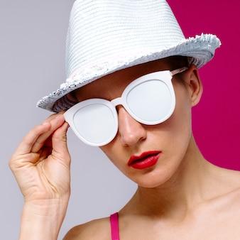 Modelo estilo pop art de óculos escuros e um chapéu. praia mínima