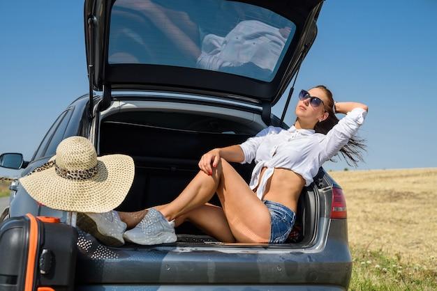 Modelo europeu lindo sexy nas férias de verão e óculos escuros posando no automóvel luxuoso na natureza na paisagem de verão.