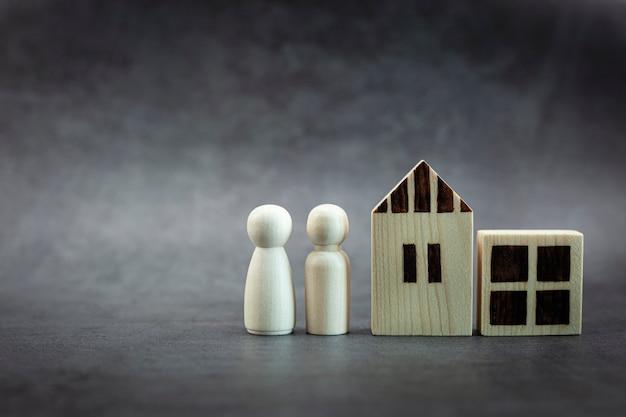Modelo familiar de pessoa de madeira e casa em fundo preto