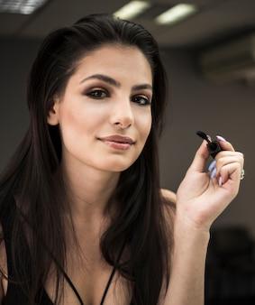 Modelo feliz em maquiagem studio