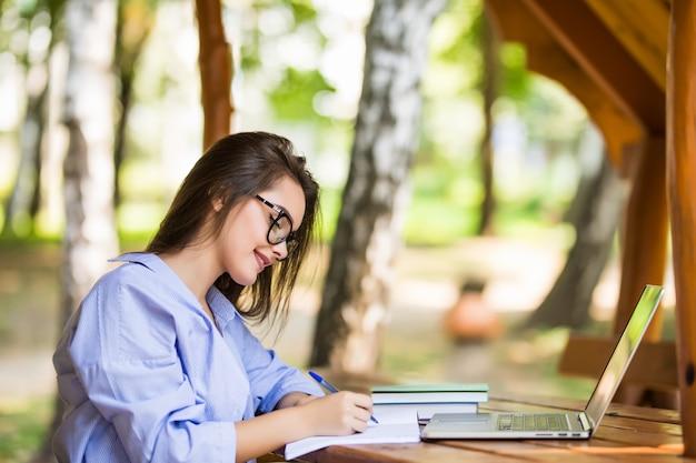 Modelo feliz usando um laptop em uma mesa do parque pela manhã