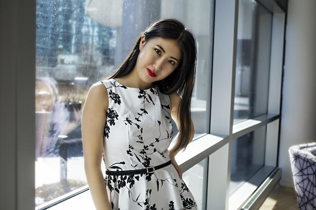 Modelo feminina asiática usando um vestido branco sexy da moda