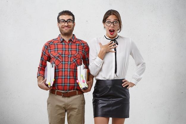 Modelo feminina chocada parece envergonhada por se esquecer de trazer a apresentação para as aulas e colega de grupo engraçada e desajeitada