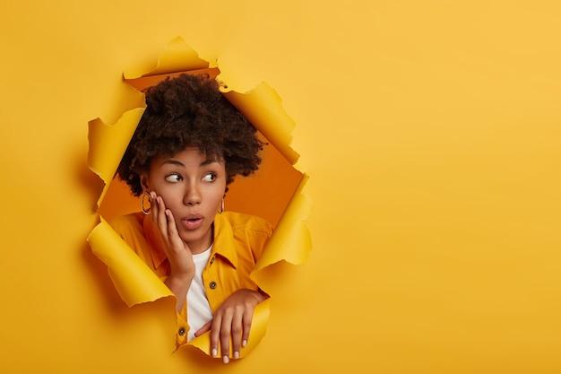 Modelo feminina de pele escura chocada olha de lado com vergonha, segura a palma da mão na maçã do rosto, surpreendida com grandes descontos, usa roupas da moda, posa no buraco do papel, fundo amarelo do estúdio