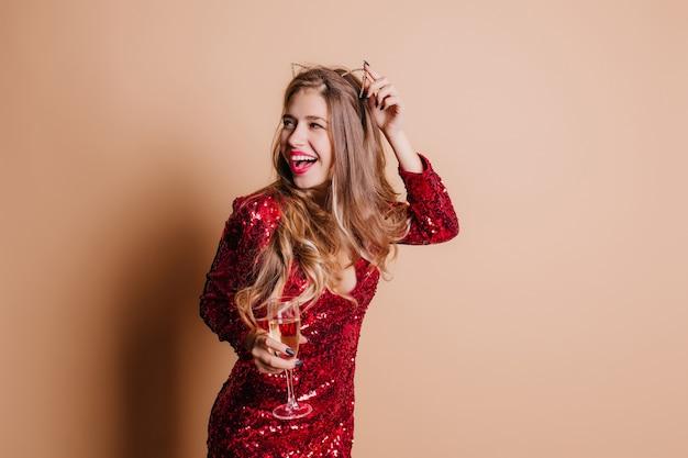 Modelo feminina deslumbrante tocando seu acessório de cabelo e olhando para longe com um sorriso