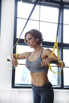 Modelo feminina fazendo atividades esportivas na academia