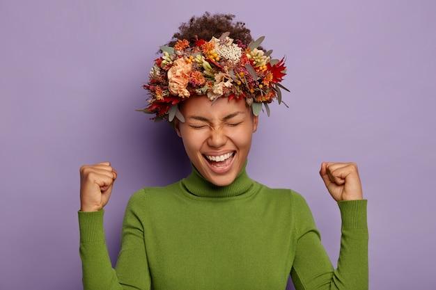 Modelo feminina feliz e radiante celebra o sucesso, ergue os punhos cerrados, ri de alegria, regozija-se com a temporada de outono, usa coroa de folhas de outono, veste um macacão verde