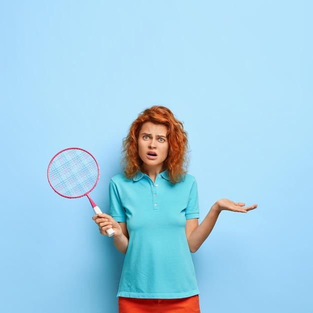 Modelo feminina insatisfeita e indignada segura raquete de tênis, gesticula com desprazer, perde o jogo, briga com o adversário