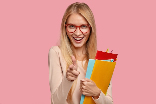 Modelo feminina loira alegre usa óculos redondos, faz gestos de arma, segura livros didáticos
