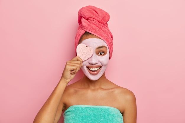 Modelo feminina satisfeita e encantada segura esponja cosmética, aplica máscara facial de argila que combina com sua pele, faz procedimentos cosméticos no banheiro