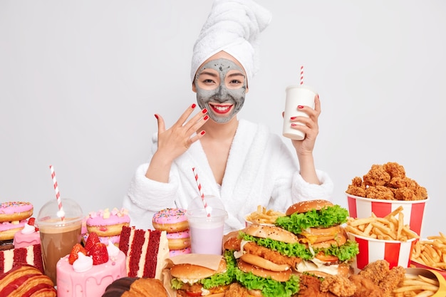 Modelo feminina satisfeita sorri e segura uma bebida rodeada de fast food