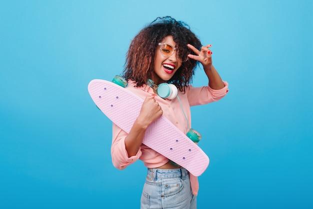 Modelo feminino africano alegre em jeans posando com o símbolo da paz segurando longboard. mulata rindo com blusa de algodão e fones de ouvido