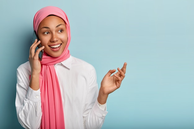 Modelo feminino alegre discute notícias incríveis com um amigo próximo, segura o smartphone perto da orelha e olha bem feliz
