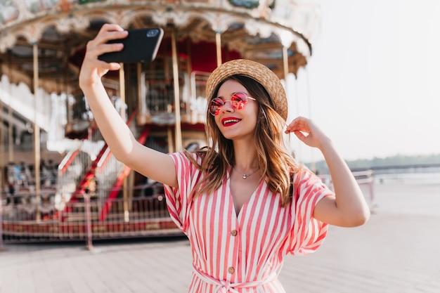 Modelo feminino alegre em traje listrado, posando perto de carrossel com chapéu de palha. tiro ao ar livre da elegante garota caucasiana usando smartphone para selfie no parque de diversões.