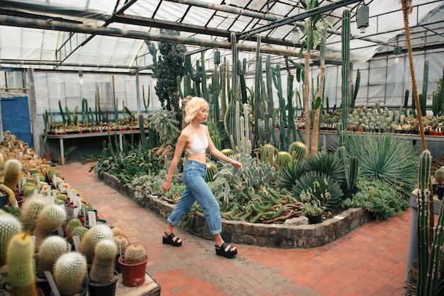 Modelo feminino andando entre plantas tropicais