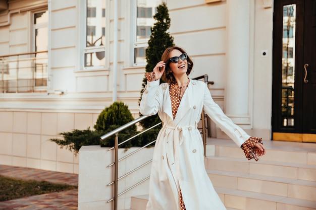 Modelo feminino animado em jaleco branco longo, aproveitando o bom dia. tiro ao ar livre de mulher jovem ativa com roupa de outono.