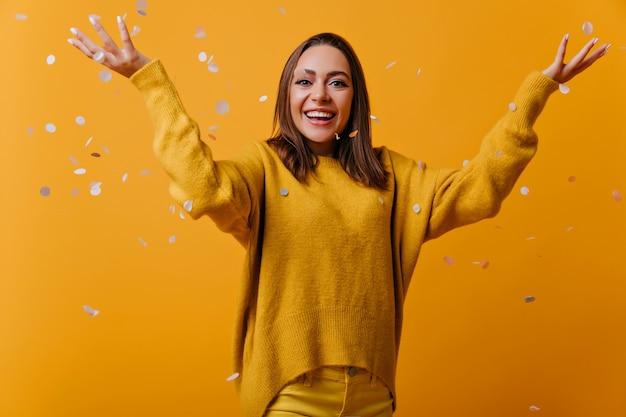 Modelo feminino animado em suéter macio amarelo sob confete. retrato de mulher alegre com cabelo escuro e liso.