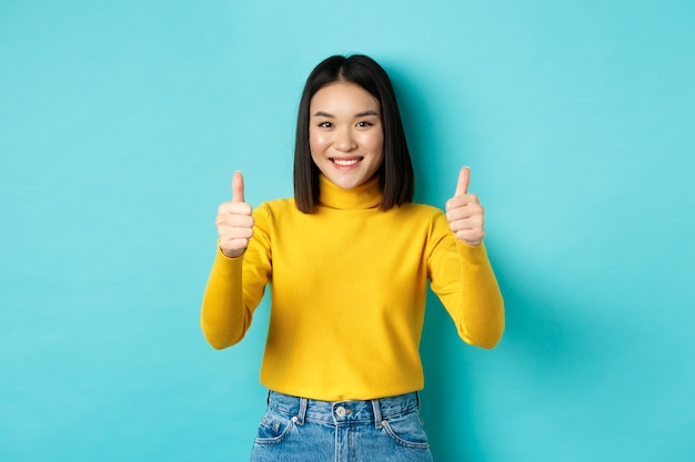 Modelo feminino asiático alegre mostrando gesto de polegar para cima, sorrindo e parecendo impressionado, elogia o bom produto, em pé sobre um fundo azul