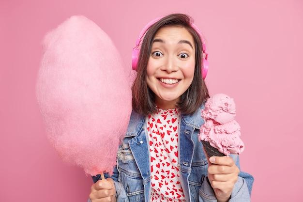 Modelo feminino asiático bonito morena positiva sorri positivamente vestida em poses de roupas da moda com deliciosas sobremesas doces apetitosas contra a parede rosa. desfrute de sorvete e algodão doce