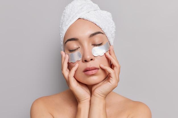 Modelo feminino asiático mantém as mãos no rosto fecha os olhos aplica manchas prateadas sob os olhos tem pele saudável corpo bem cuidado usa toalha enrolada na cabeça poses em cinza