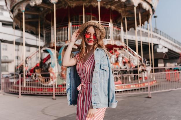 Modelo feminino bem-humorado com chapéu de palha, relaxando perto do carrossel. menina despreocupada na moda, passando o dia no parque de diversões.