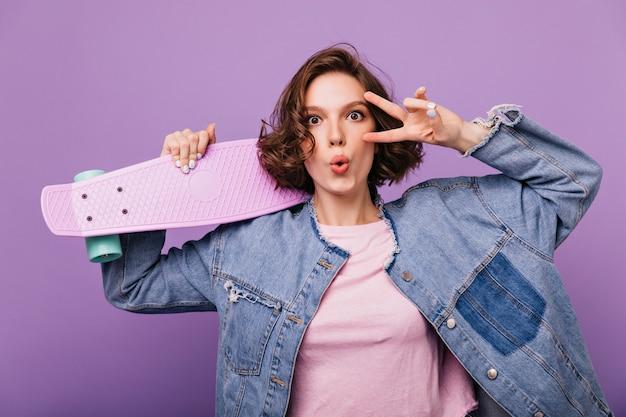 Modelo feminino bem humorado com corte de cabelo curto posando com skate. senhora bonita caucasiana em traje jeans, segurando longboard.