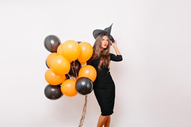 Modelo feminino bem torneado com chapéu de bruxa sorrindo antes da festa de halloween