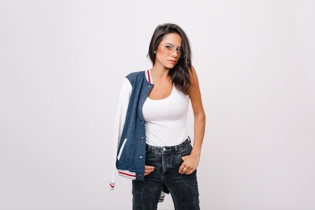 Modelo feminino branco sério em copos em pose confiante com as mãos nos bolsos.