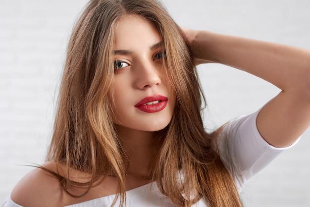 Modelo feminino caucasiano atraente em top branco usando olho maquiagem e batom vermelho
