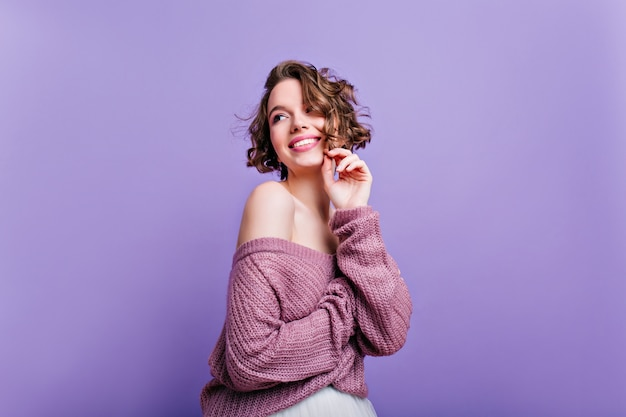 Modelo feminino caucasiano inspirado com corte de cabelo curto, olhando para longe com um sorriso tímido na parede roxa. foto de uma adorável mulher de cabelos castanhos em uma camisola relaxante na sessão de fotos.