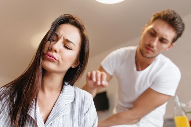 Modelo feminino chateado com um pijama fofo, posando com os olhos fechados enquanto um homem caucasiano diz algo
