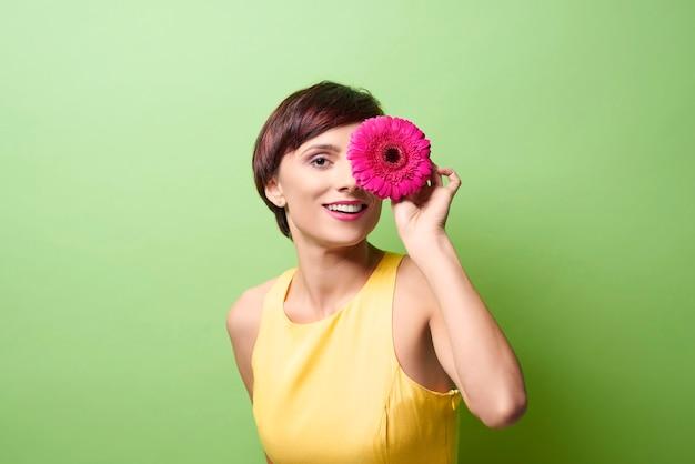 Modelo feminino cobrindo o olho com uma flor