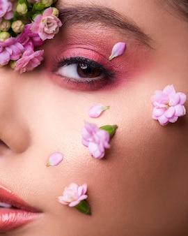 Modelo feminino com flores na cara dela
