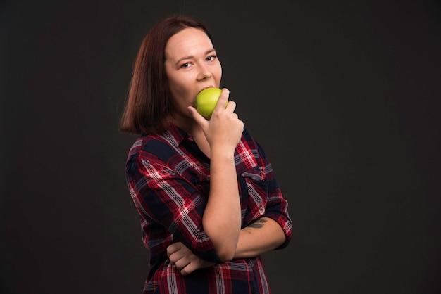 Modelo feminino com roupas de coleção outono inverno segurando uma maçã verde e dando uma mordida.