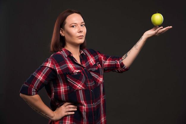 Modelo feminino com roupas de coleção outono inverno, segurando uma maçã verde na mão aberta.