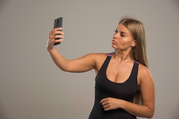 Modelo feminino com sutiã esportivo tirando uma selfie