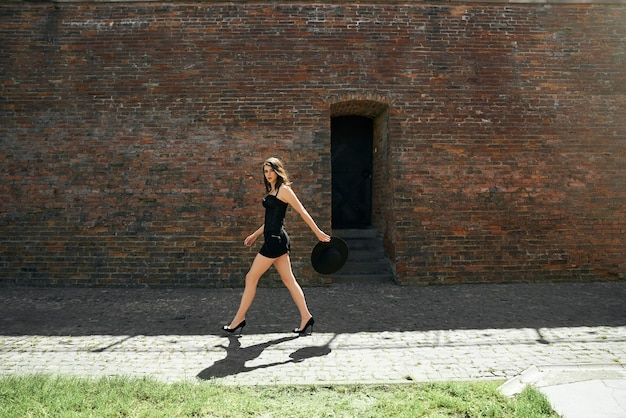 Modelo feminino com vestido preto, andando perto da parede de tijolos.