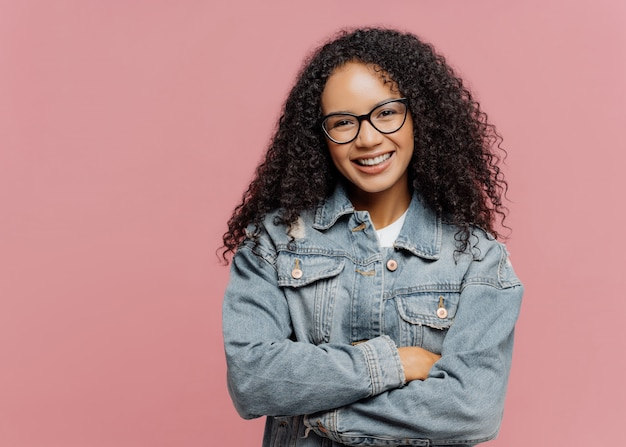 Modelo feminino de aparência agradável e alegre usa óculos ópticos e jaqueta jeans, mantém os braços cruzados sobre o peito