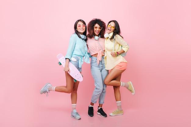 Modelo feminino de cabelos negros entusiasmados com lindo bronzeado em pé em uma perna enquanto seus amigos sorriem. alegre mulher africana em jeans e sapatos pretos, se passando perto da garota skatista de camisa azul.
