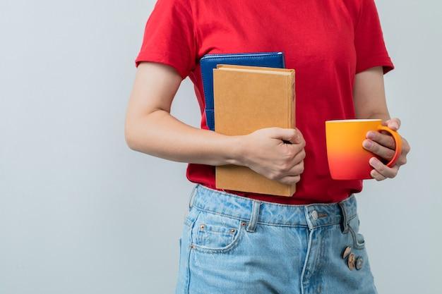 Modelo feminino de camisa vermelha, segurando livros e um copo de bebida.