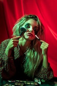 Modelo feminino de halloween brincando com pincéis de pó