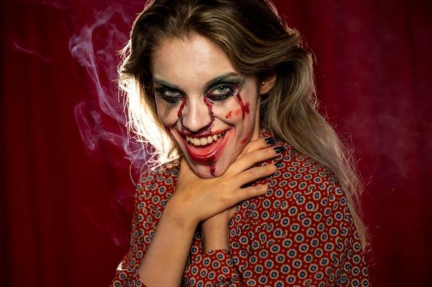 Modelo feminino de halloween, sufocando com as próprias mãos
