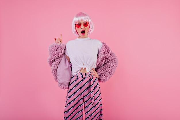 Modelo feminino desagradável posando na moda jaqueta fofa. garota atraente e desapontada com peruca rosa isolada em parede colorida