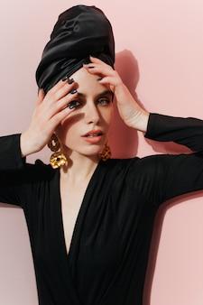 Modelo feminino elegante com turbante olhando para a câmera
