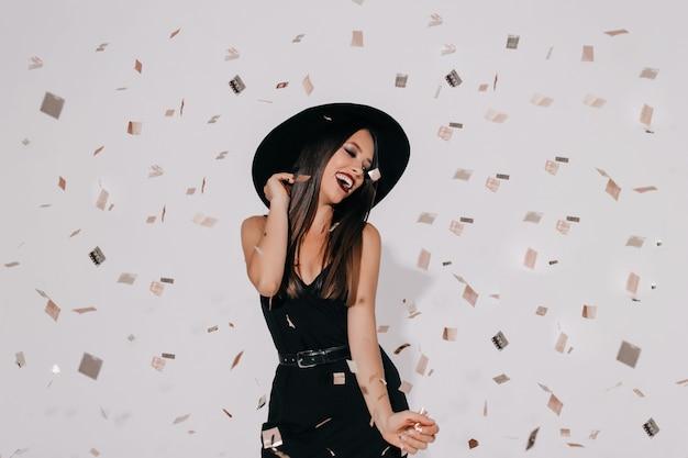 Modelo feminino elegante e atraente com fantasia de bruxa se preparando para a festa de halloween na parede isolada com confete dançando, se divertindo, sorrindo.