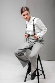 Modelo feminino elegante em elegante camisa branca e suspensórios. novo conceito de feminilidade