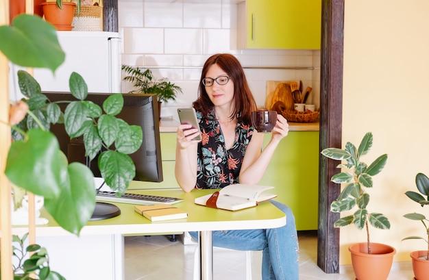 Modelo feminino em casa escritório usando seu computador e bebendo café