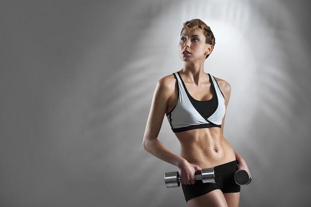 Modelo feminino em forma e tonificada segurando halteres de ginástica