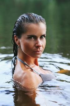 Modelo feminino em maiô preto no lago
