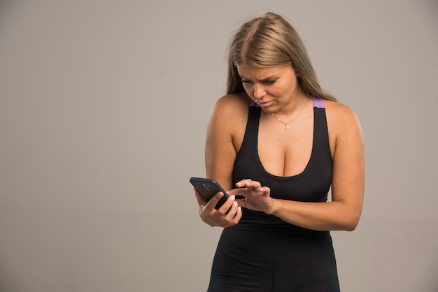 Modelo feminino em mensagens de texto de sutiã esporte com seu smartphone e parece sério.